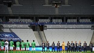 Les joueurs du Paris Saint-Germain et de Saint-Etienne durant la minute d'applaudissements en mémoire des victimes du Covid-19 avant la finale de la Coupe de France de football dans un stade avec peu de spectateurs le 24 juillet 2020 à Saint-Denis