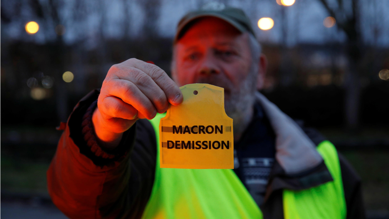 "Un ""chaleco amaraillo"" pausa con un escrito ""Macron dimisión"", cerca de una glorieta que ocupa en Gaillon, Francia, el 6 de diciembre de 2018."