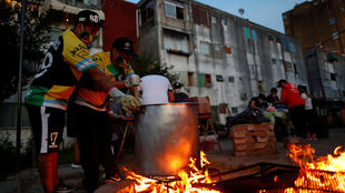Unos hombres que usan mascarillas como protección contra la enfermedad por coronavirus preparan un guiso para ayudar a las personas de bajos ingresos en Fuerte Apache, a las afueras de Buenos Aires, Argentina, el 23 de abril de 2020.