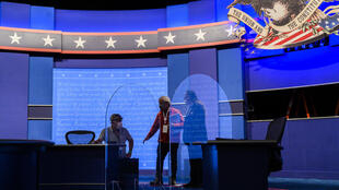 Workers install plexiglass protections on the stage of the debate hall ahead of the vice presidential debate in Kingsbury Hall of the University of Utah