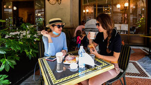 Women have coffee and pastry at Cafe Some Milan residents availed themselves of the chance to enjoy a coffee and pastry on a cafe terrace for the first time after two months in lockdown