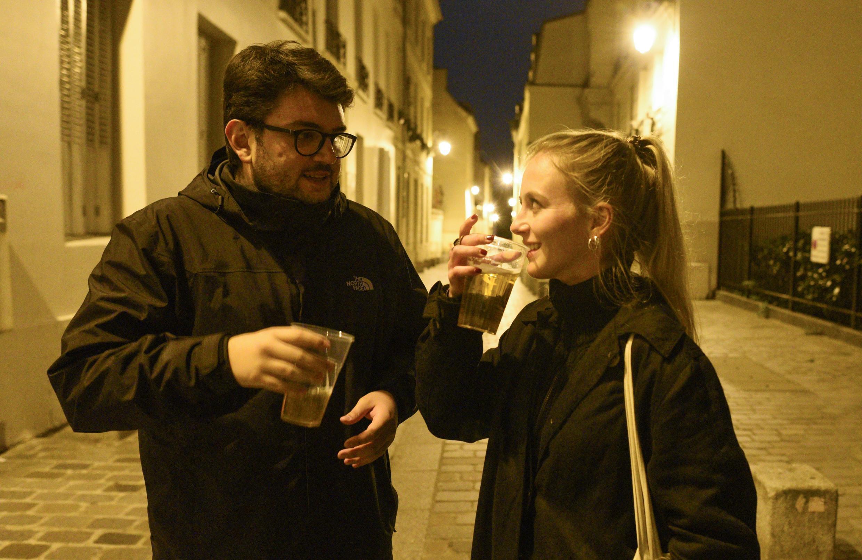 Giulano Binda et Isabella Foglia, deux étudiants suisses, dégustent leur dernier verre dans un gobelet en plastique à l'extérieur après la fermeture des bars pour le verrouillage du Covid-19 le 17 octobre à Paris.