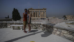 A couple takes selfie next to a sticker marking social distance in front of the Parthenon
