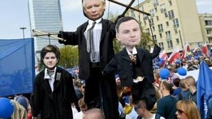 متظاهرون يرفعون صورا للرئيس البولندي ياروسلاف كاتشينسكي رئيسة الوزراء بياتي شيدلو والرئيس اندري دودا خلال احتجاجاتهم على مشاريع قوانين في 06 أيار/مايو 2017
