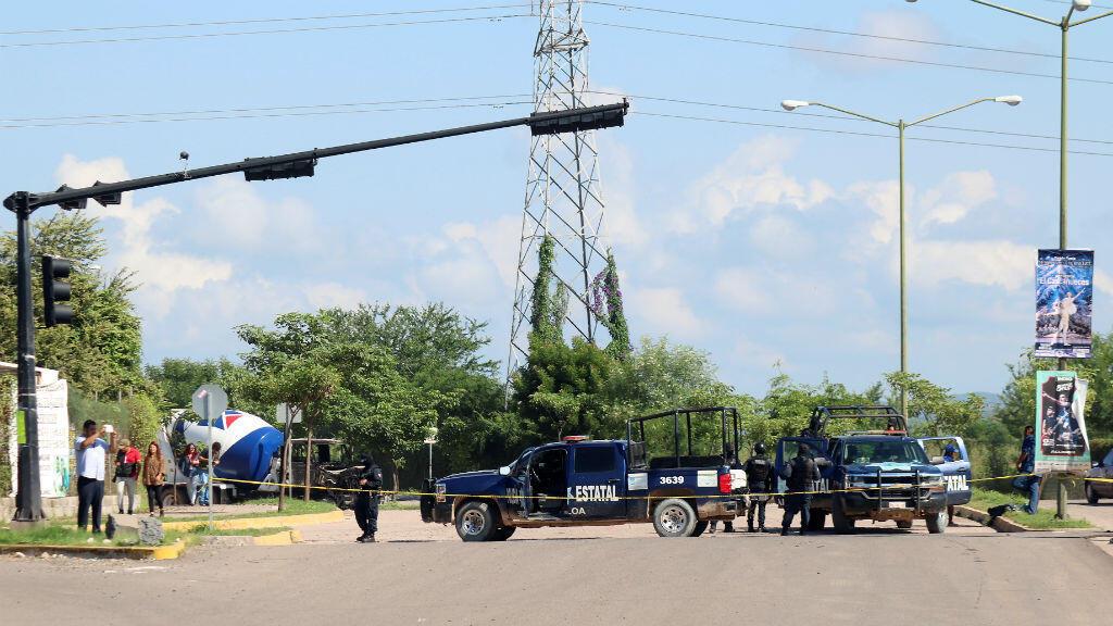 Los oficiales de policía vigilan en una calle un día después de que hombres armados del cártel se enfrentaran con las fuerzas federales, en Culiacán, en el estado de Sinaloa, México, el 18 de octubre de 2019.