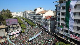 Más de mil personas portan banderas y pancartas nacionales durante una protesta para exigir la renuncia del presidente Abdelaziz Bouteflika, el 29 de marzo de 2019.
