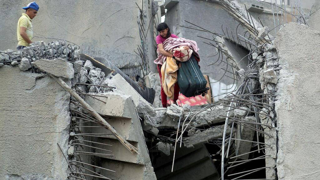 Una pareja de palestinos buscan lo que queda de sus pertenencias luego de que su casa quedara destruida tras los bombardeos. Ciudad de Gaza, mayo 7 de 2019.