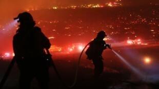 Los bomberos caminan hacia la línea de fuego en Lilac en Bonsall, California, el 7 de diciembre de 2017.