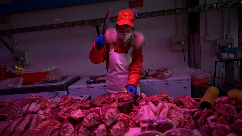 Una empleada corta carne en el mercado mayorista de Xinfadi, con el país afectado por un brote de la nueva enfermedad por coronavirus, en Beijing, China, el 19 de febrero de 2020.
