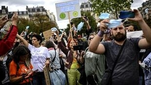 Protesters hold up face masks and shout slogans during a protest against the mandatory wearing of face masks on the Place de La Nation in Paris on August 29 2020.