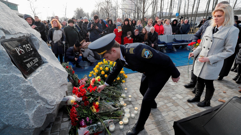 Familiares y amigos depositan flores en una piedra conmemorativa y rinden homenaje durante la ceremonia de fundación de un monumento en memoria de las víctimas del vuelo de Ukraine International Airlines (UIA) que se estrelló en Irán, en el aeropuerto internacional de Boryspil en Kiev, Ucrania, el 17 de febrero. 2020 (reeditado el 18 de julio de 2020). Foto de archivo.