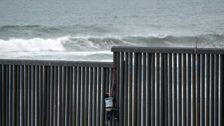 مهاجر من أمريكا الوسطى يتسلق سياجا حدوديا للعبور من تيخوانا المكسيكية إلى سان دييغو الأمريكية في 21 آذار/مارس 2019