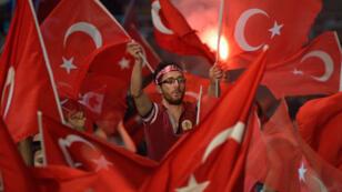 Un partisan du président Erdogan, au milieu des drapeaux turcs, place Taksim à Istanbul, mardi 19 juillet.