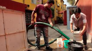 Repartidores de agua potable descargan el líquido entre los habitantes de una colonia en Ciudad de México (México), tras el corte por obras de mantenimiento que se extenderá por cuatro días.