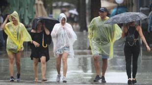 Peatones caminan bajo la lluvia de la tormenta tropical Gordon en Miami Beach, Florida. 3 de septiembre de 2018.