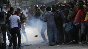 Des manifestants se réfugient derrière un camion anti-émeutes de la police nationale d'Haïti, le 11 octobre.