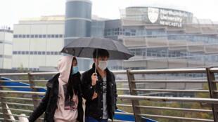 Una pareja con mascarilla pasea bajo la lluvia frente a la sede de la Universidad de Northumbria, el 3 de octubre de 2020 en Newcastle, al noreste de Inglaterra