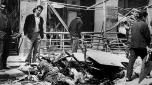 Des passants regardent les débris d'une voiture piégée , Place de la République à Alger le 26 avril 1962, après une explosion ayant causé la mort de deux personnes et fait un grand nombre de blessés.