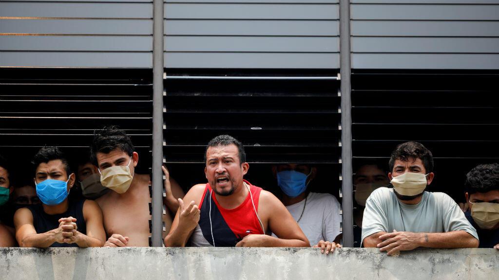 Las personas, que fueron detenidas por violar las medidas de cierre nacional de El Salvador, hablan con los medios de comunicación mientras protestan después de que las autoridades gubernamentales no los liberaron a pesar de haber cumplido su cuarentena obligatoria en un centro de detención en San Salvador, El Salvador, el 4 de mayo de 2019.