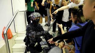 Un policía antidisturbios detiene a un manifestante en un centro comercial de Hong Kong, el 3 de noviembre de 2019.