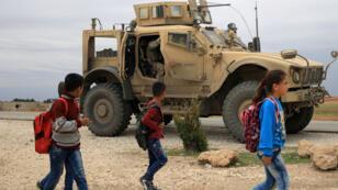 Des écoliers marchent près d'un véhicule de l'armée américaine en Syrie, près de la frontière turque.