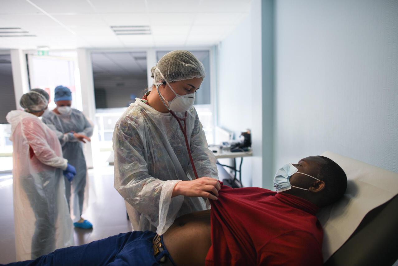 Le docteur Pascaline Mourey ausculte Christian Edimo, un homme de 47 ans qui présente plusieurs symptômes du Covid-19