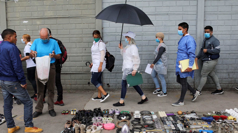 Los médicos caminan frente a los vendedores ambulantes durante una caminata mientras los casos aumentan en medio del brote de la enfermedad por coronavirus, en Caracas, Venezuela, 14 de julio de 2020. Fotografía tomada el 14 de julio de 2020.