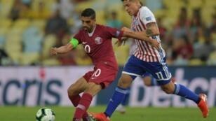 قائد منتخب قطر حسن الهيدوس (يسار) في صراع على الكرة مع لاعب باراغواي خوان إيتوربي خلال لقاء الفريقين في كوبا أمريكا. 16 حزيران/يونيو 2019.