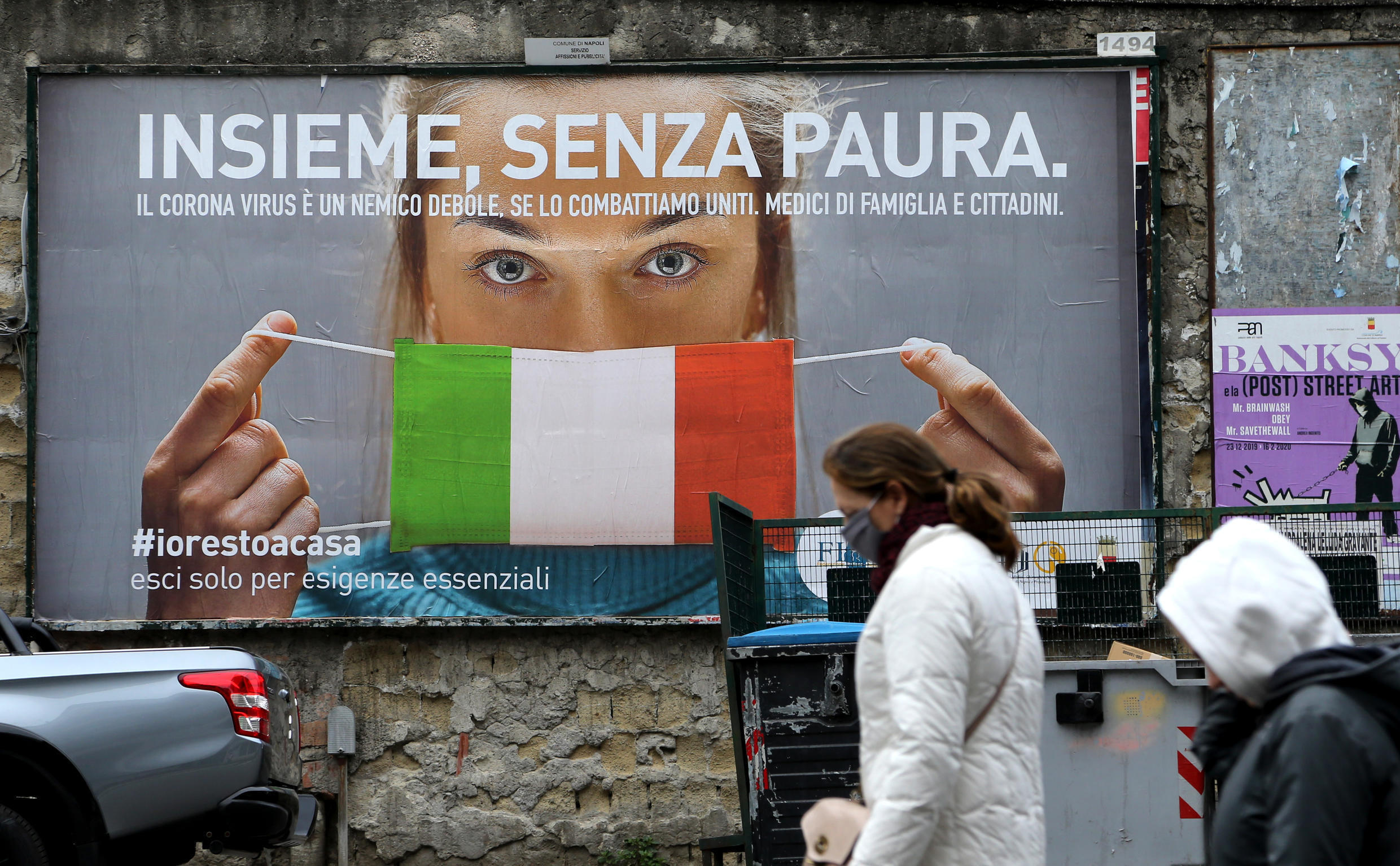 A billboard showing a woman with a protective mask in the colours of the Italian flag pictured in Naples on March 22, 2020.