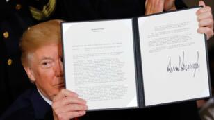 El presidente Donald Trump enseña la declaración firmada de emergencia sanitaria pública. 26/10/2017
