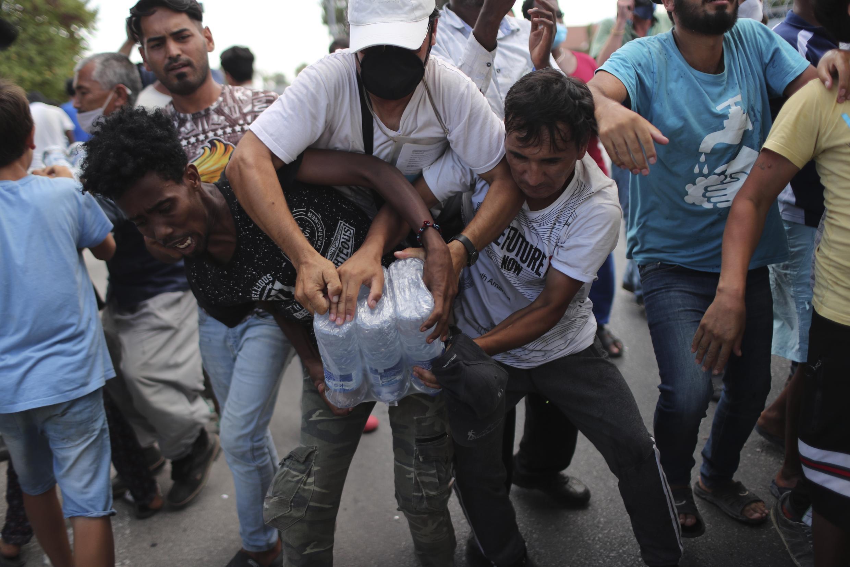 Migrantes se pelean para llevarse botellas de agua durante una distribución por parte de las autoridades locales cerca de la ciudad de Mytilene, en la isla nororiental de Lesbos, Grecia, el sábado 12 de septiembre de 2020.