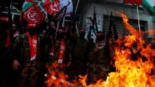 Militantes palestinos del Frente Popular para la Liberación de Palestina (FPLP) queman representaciones de una bandera israelí y una bandera de EE. UU. durante una protesta contra la decisión de Trump de reconocer a Jerusalén como la capital de Israel, en la ciudad de Gaza 7 de diciembre de 2017.