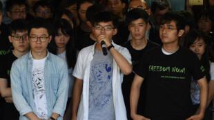 Joshua Wong et deux autres leaders s'adressant aux médias avant d'entendre le verdict du tribunal.
