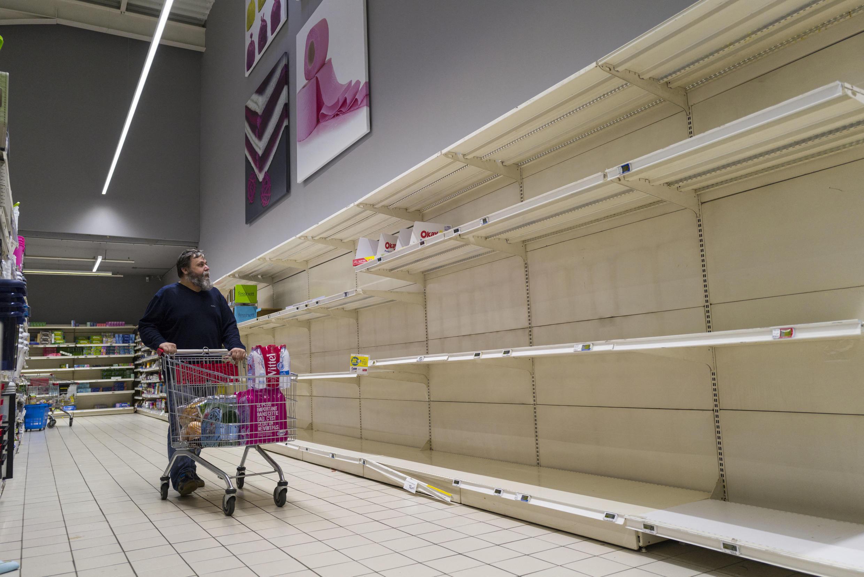 Un homme cherchant du regard du papier toilette dans un supermarché le 16 mars 2020, à Pfastatt, dans l'est de la France, à l'heure où certains ont déjà fait le plein de marchandises, effrayés par l'épidémie de Covid-19.