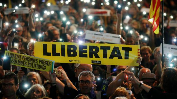 Cientos de personas encienden sus teléfonos en una protesta convocada por la Asamblea Nacional Catalana y por Omnium Cultural para conmemorar un año del encarcelamiento de sus líderes Jordi Sànchez y Jordi Cuixart. Plaza Cataluña, Barcelona, el 16 de octubre de 2018.