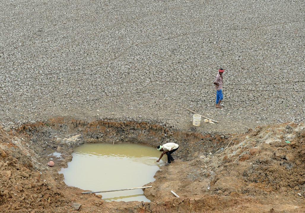 Un Indien collecte de l'eau du lac Puzhal, quasiment à sec, le 20 juin 2019.