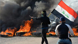 A demonstrator holds an Iraqi flag near burning tires during ongoing anti-government protests in Nassiriya, Iraq November 24, 2019.