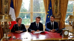 Emmanuel Macron signe les ordonnance de la réforme du droit du travail entouré de  la ministre du Travail Muriel Pénicaud et du porte-parole du gouvernement Christophe Castaner.