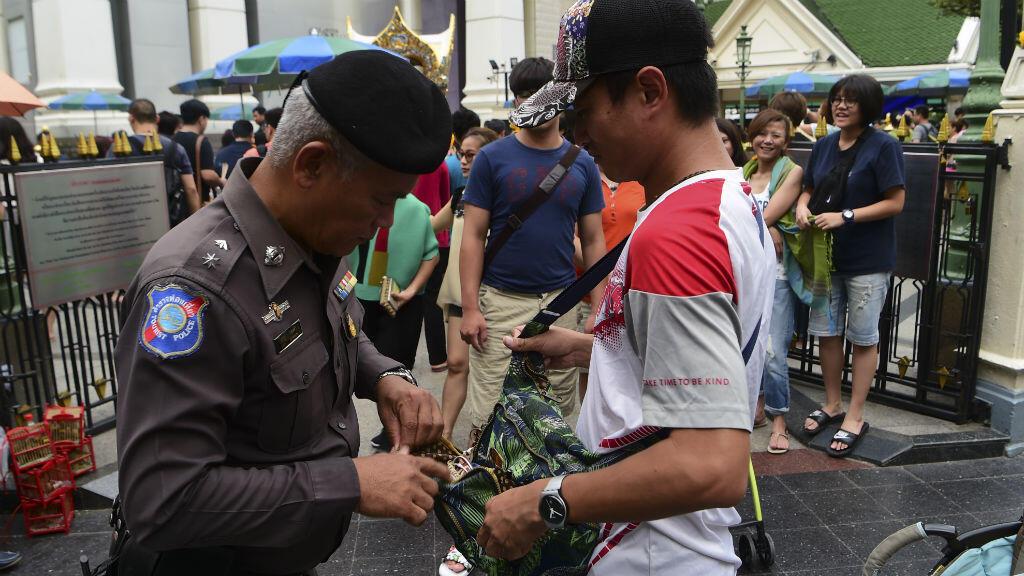 Un policier thaïlandais contrôlant un passant après la série d'explosions survenues dans des stations balnéaires du pays.