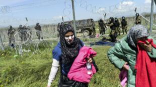 Des femmes se protègent des gaz lacrymogènes, tirés par la police macédonienne, avec du dentifrice, le 10 avril 2016 à la frontière avec la Grèce.