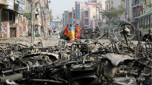 Women walk past charred vehicles in a riot-affected area following clashes between people demonstrating for and against a new citizenship law in New Delhi, India, on February 27, 2020.