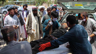 A  man injured in an explosion at a cattle market is brought to in Lashkar Gah, Helmand province