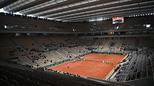 Quiet Sunday: A few spectators sit in empty stands on Court Philippe Chatrier