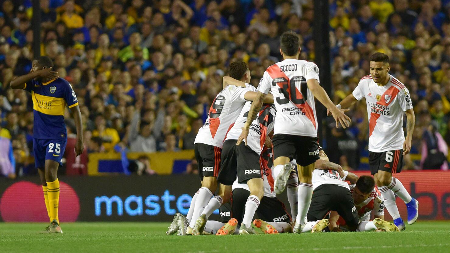 Las dos caras de la moneda: los jugadores de River Plate festejan la clasificación a la final de la Copa Libertadores y el jugador venezolano de Boca Juniors, Jan Hurtado, se lamenta tras el partido en La Bombonera, en Buenos Aires, el 22 de octubre de 2019.