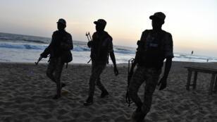 Des soldats ivoiriens marchent sur la plage à Grand-Bassam, le 13 mars 2016, après l'attaque terroriste.