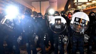 Des policiers lors d'une manifestation contre un projet de loi controversé sur l'extradition, à Hong Kong, le 21 juillet 2019.