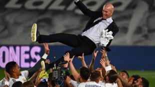 لاعبو ريال مدريد يحتفون بمدربهم الفرنسي زين الدين زيدان بعد الفوز بلقب الدوري الإسباني لكرة القدم، في 16 تموز/يوليو 2020.