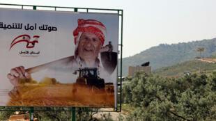 صورة تم التقاطها في 8 نيسان/أبريل 2018، من الجانب اللبناني في قرية كفاركيلا على الحدود اللبنانية مع إسرائيل، تظهر ملصقا انتخابيا.