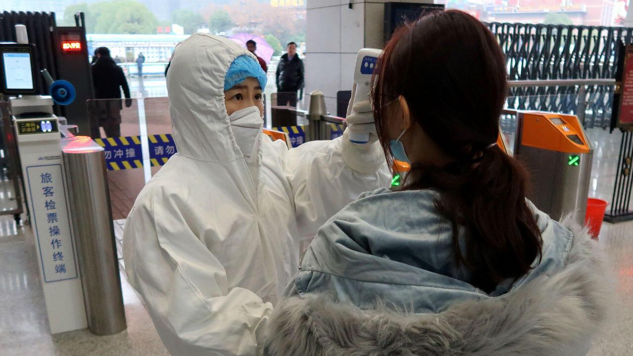 Un funcionario verifica la temperatura de los pasajeros que llegan a la estación Xianning North en Xianning, China, el 24 de enero de 2020.