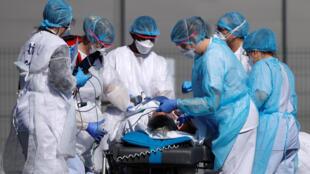 De médecins s'occupent d'un patient de l'hôpital de Mulhouse avant qu'il ne soit transféré par hélicoptère, le 23 mars 2020.